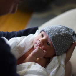 fathers holds newborn baby photosession in home