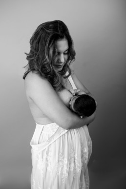 Mother and baby breastfeed during photo shoot in studio