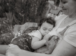 Mother and toddler breastfeed while sitting on a bench in the garden; toddler sleeps