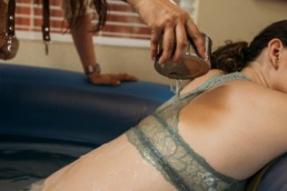 Photo of doula pouring warm water over a woman's back who is in labor. Mother leans over the side of birth tub and relaxes in between contractions