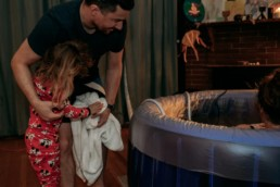 Father and sister look into birth tub at newborn baby