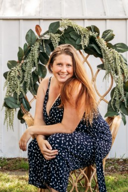 Woman posed sitting in chair surrounded by flowers smiles at the camera